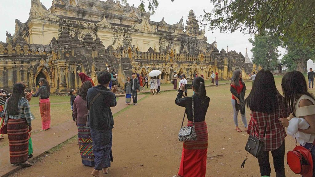 Visitors to Aungmyebonzan Monastery take pictures with the rare architecture of the buildings in the background. Photo: Than Zaw Min (IPRD)