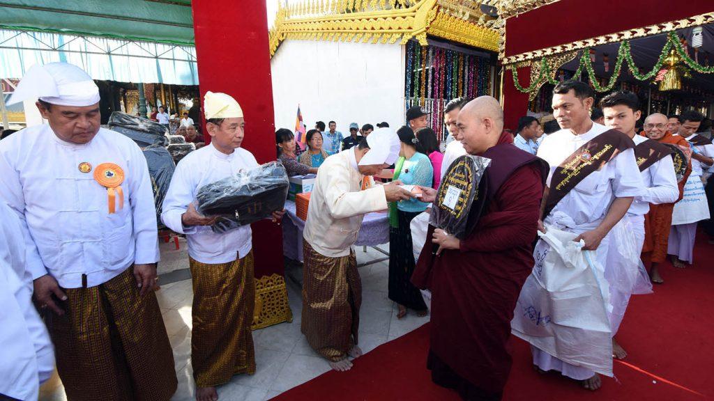 Union Minister Thura U Aung Ko donates offertory to a Sayadaw at the ceremony to mark 100th anniversary of Shwedagon Cetiyingana examination at Shwedagon Pagoda yesterday.Photo: MNA