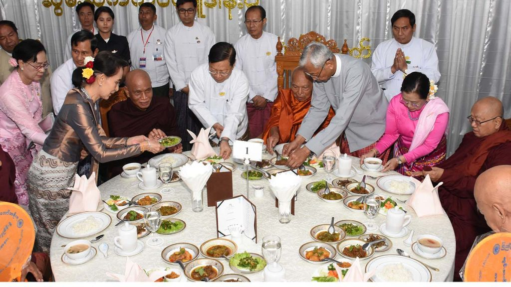 President U Htin Kyaw, third from right, First Lady Daw Su Su Lwin, second from right, and State Counsellor Daw Aung San Suu Kyi, first from left, offer a midday meal to members of the Sangha in Nay Pyi Taw yesterday, including Sayadaws who will receive religious titles.Photo: MNA