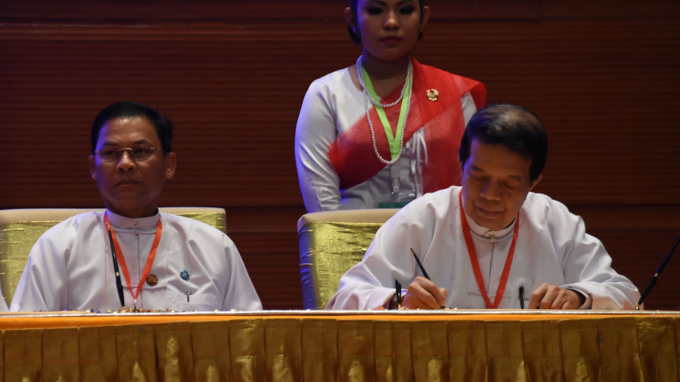 Peace Commission Chairman Dr. Tin Myo Win signs Nationwide Ceasefire Agreement. Photo: MNA