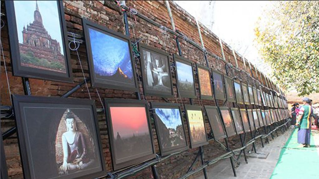 A guest views old and new photos of Bagan and its temples at a photo exhibition in Bagan. Photo: Mdn