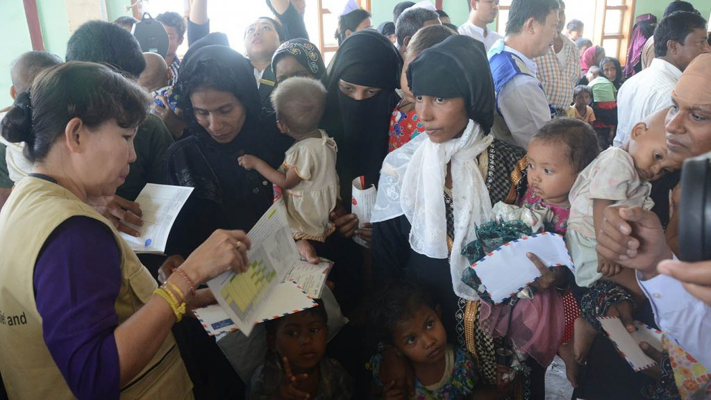 Mothers gather to receive financial aid to be used for supplementary nutrition for their children in Maungtaw, Rakhine State, yesterday.Photo: MNA