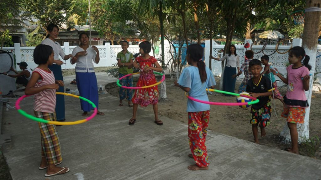 Children playing with hula hoops as part of physical development activities in Dala Township's IPRD community centre.  Photo: Naing Lin Kyaw (Dala)