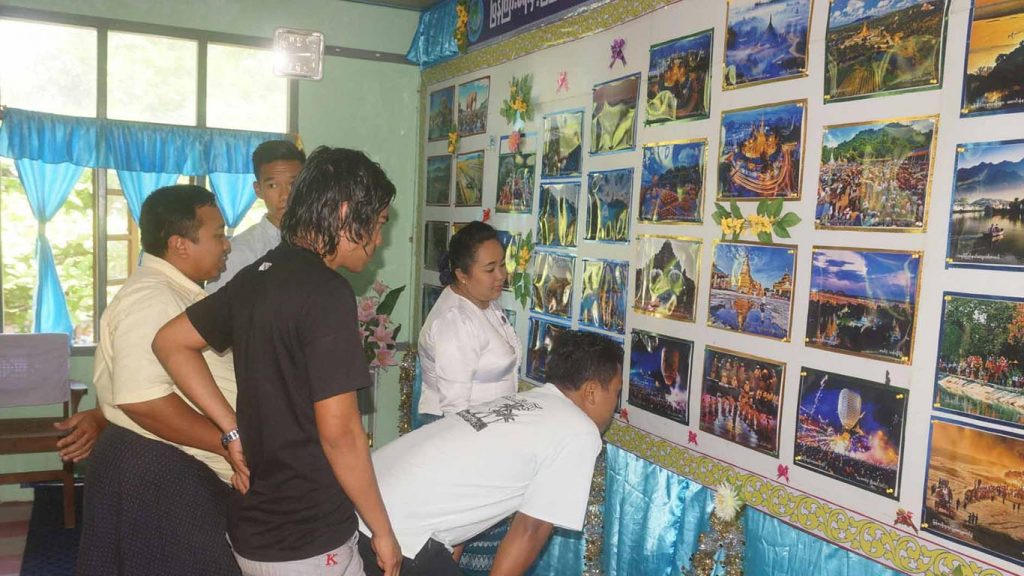 Visitors look at the displayed photos at photo exhibition at Community Centre in Rakhine State.Photo: MNA