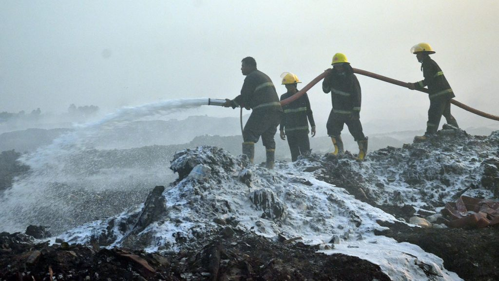 Fire fighters douse bio foam over the garbage dump to control poisonous smoke in Hlinethaya. Photo: Zaw Gyi