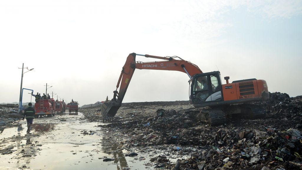 A back hoe clears a path through the garbage dump for firefighters to reach afflicted areas. photo: pe zaw