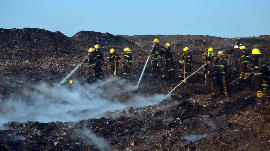 Firefighters douse the garbage dump with bio foam and water to extinguish the underground fire. photo: pe zaw
