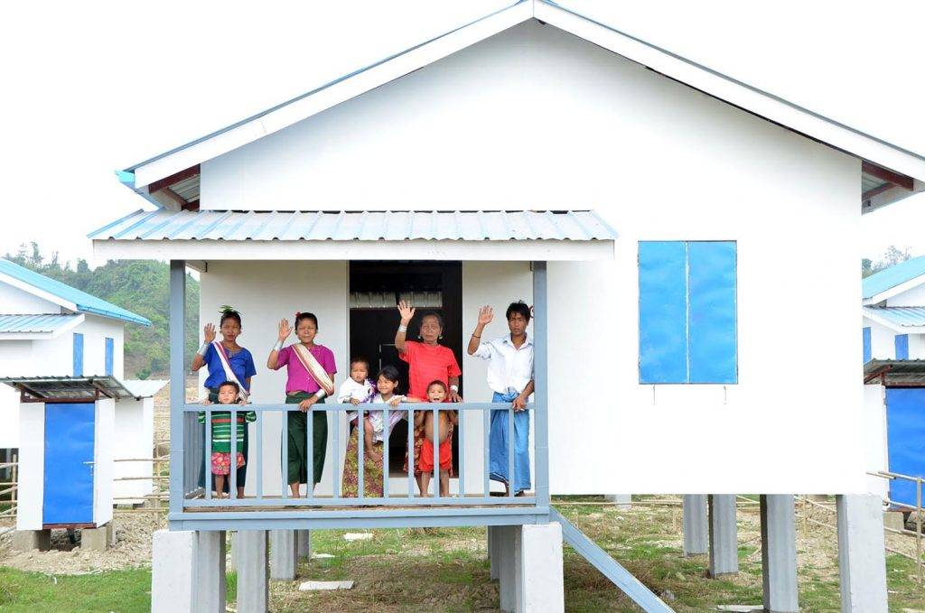 A Mro family waves from their new house in Kontaing Village. Photo: Tin Soe