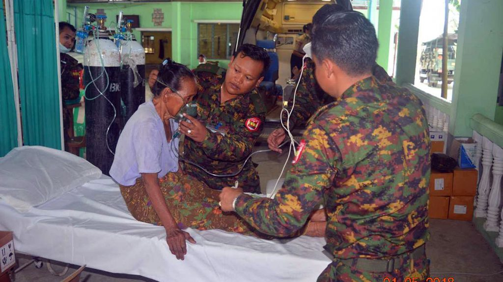 Tatmadaw officers providing medical treatment to local resident affected by garbage dump fire.Photo: Zaw Gyi