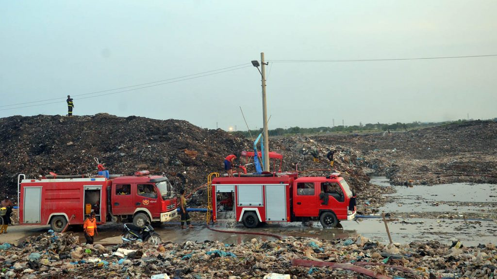 Firefighters survey a zone in Htein Bin garbage dump for heat and gas emissions. Photo: Pe Zaw