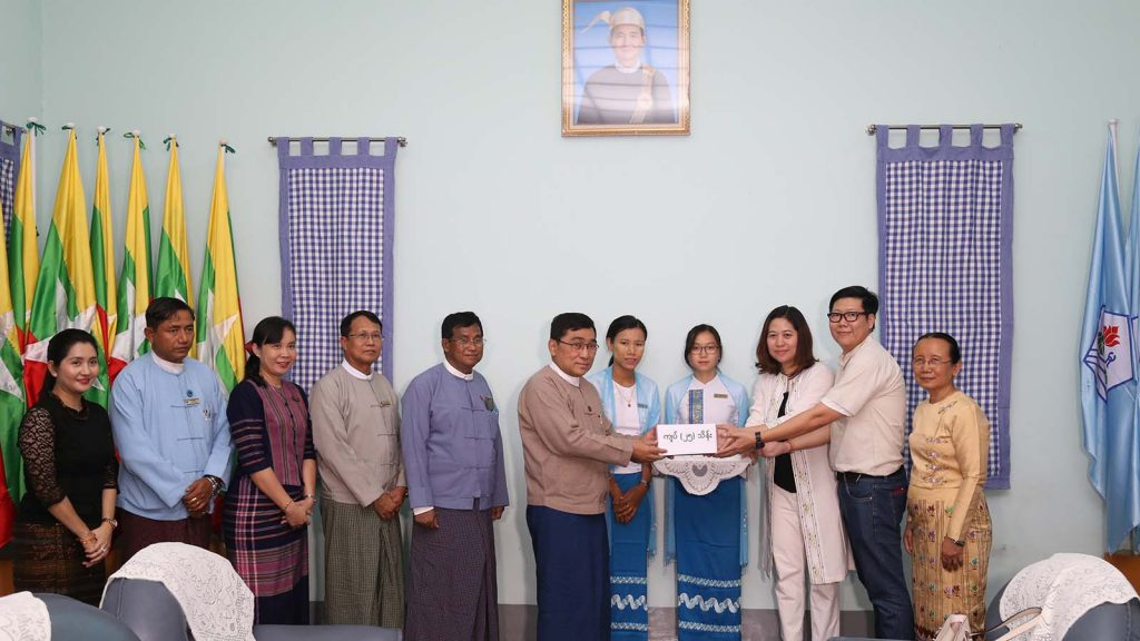 Union Minister Dr. Win Myat Aye accepts a donation for displaced persons in Kachin State. photo: mna