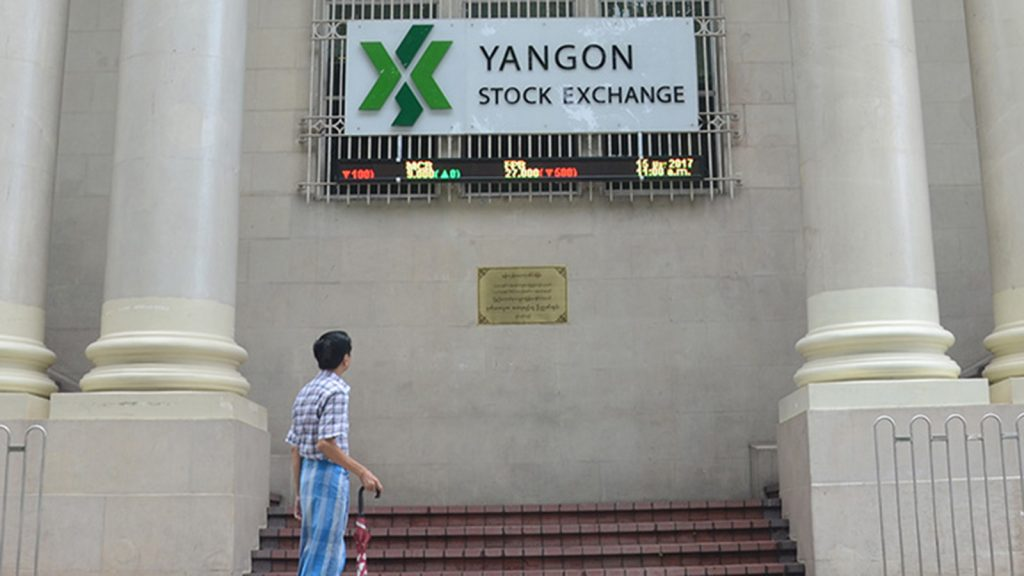 A man looks at the LED board showing the stock exchange rates at YSX, in Yangon. Photo: Supplied