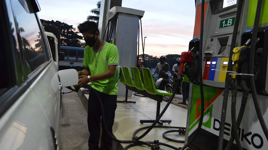 An employee at a fuel station fills up a car's oil tank. Photo: Phoe Khwar