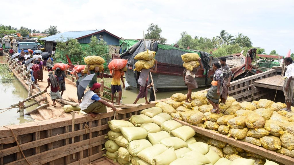 Workers at the Maungtaw border trade camp load up a boat with bags of ginger, which has seen the most increase in export value in the current months, followed by exports of other agricultural products, fishery products, forestry products and industrial products. photo: hein HTET lin, myo thu hein