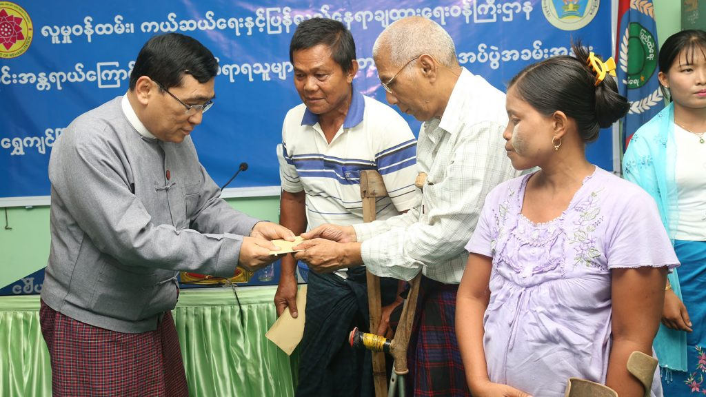 Union Minister Dr. Win Myat Aye donate cash to flood-affected people in Shwekyin. Photo: MNA