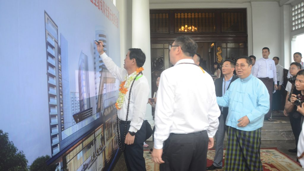 Hunan province Vice Governor He Baoxiang signs on the vinyl sheet depicting the Yangon New World project.Photo: Min Thit (MNA)