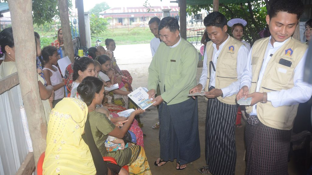 Pregnant women and children receive cash from officials.  Photo:  Hein Htet Zaw (Myanma Alinn)