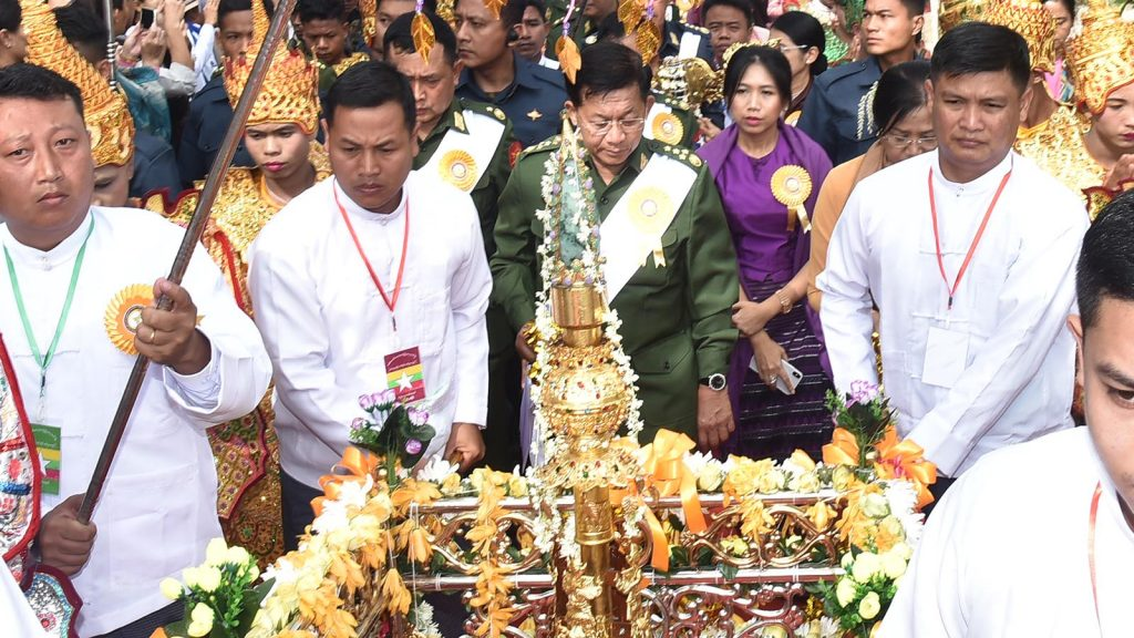 Senior General Min Aung Hlaing and wife Daw Kyu Kyu Hla carry religious objects.Photo: C-in-c office