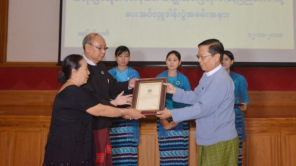 Union Minister Thura U Aung Ko presents certificate of honour to Amyotha Hluttaw Speaker Mahn Win Khaing Than for donation of martyr Mahn Ba Khaing's Kayin national dress in Nay Pyi Taw. Photo: MNA