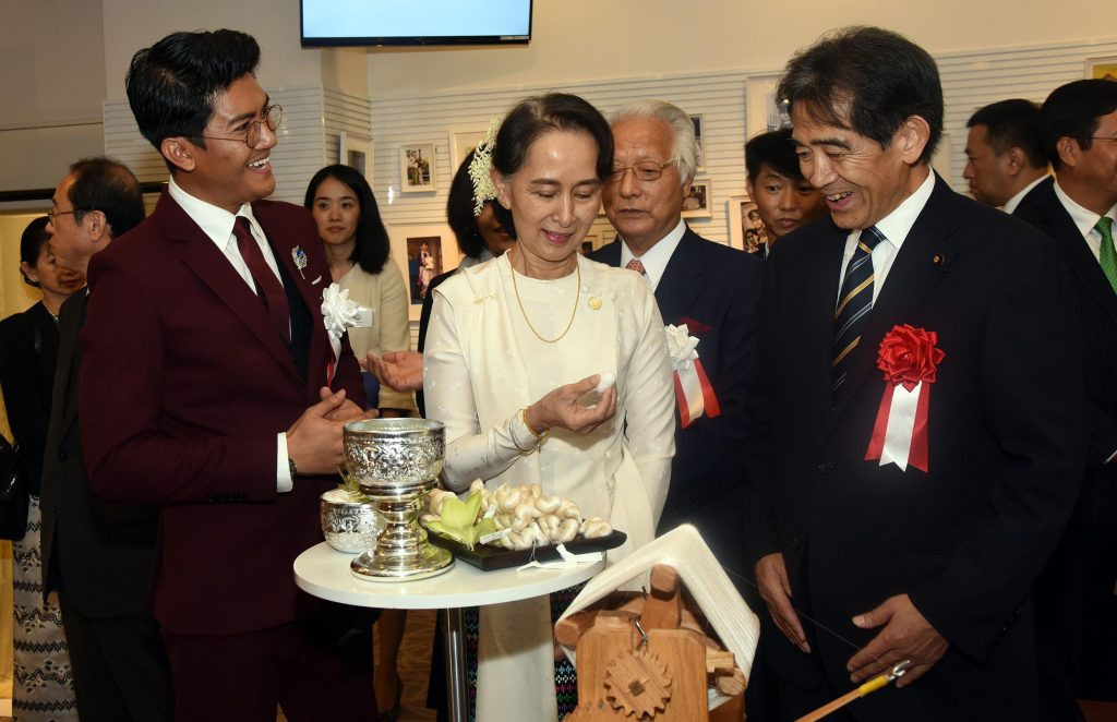 State Counsellor Daw Aung San Suu Kyi observes a silk loom and silk cacoon display at the Myanmar Silk Promotion Event held at the ASEAN-Japan Centre yesterday. Photo: MNA