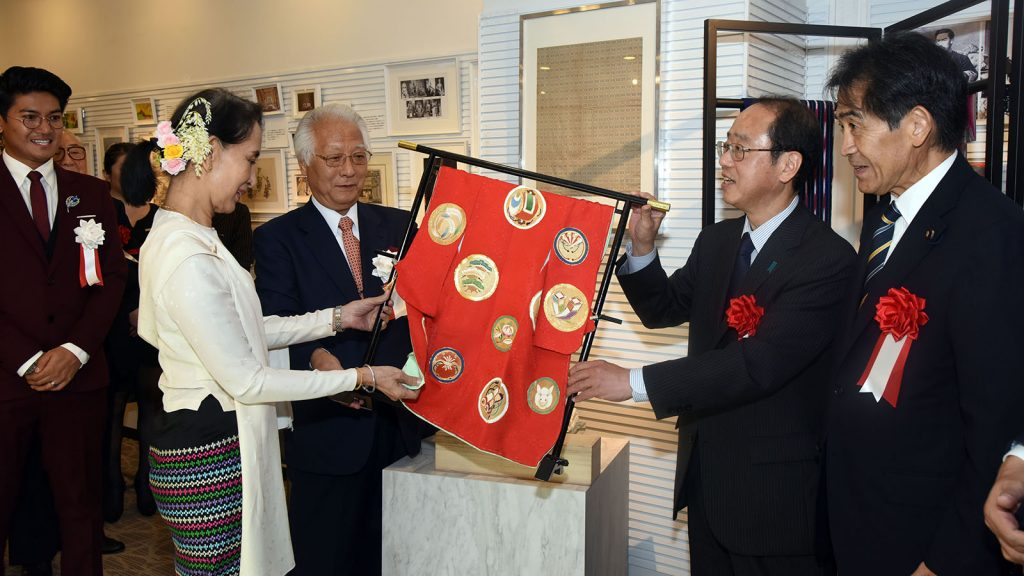 State Counsellor Daw Aung San Suu Kyi observes a piece of silk cloth woven with Japanese designs at the Myanmar Silk Promotion Event at the ASEAN-Japan Centre in Japan yesterday. Photo: MNA