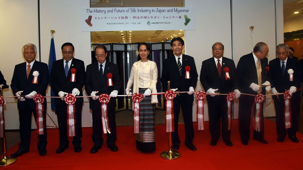State Counsellor Daw Aung San Suu Kyi cuts the ceremonial ribbon alongside Japanese high-level officials to open the Myanmar Silk Promotion Event at the ASEAN-Japan Centre in Japan.  photo: mna
