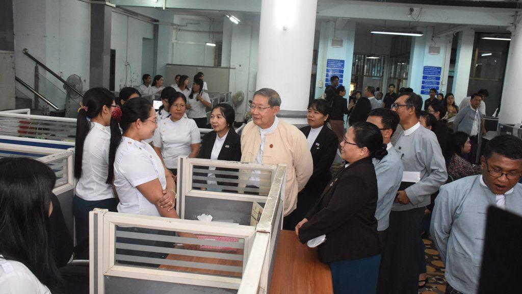 Union Minister U Soe Win greeting MFTB staffs in Kyauktada Township, Yangon yesterday.Photo: Zaw Min Latt