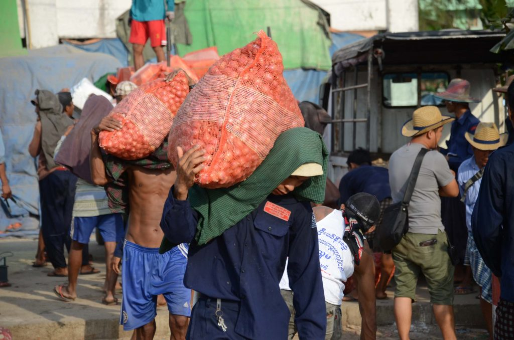 Labourers carrying sacks of onions on their shoulders. Photo: Phoe Khwar