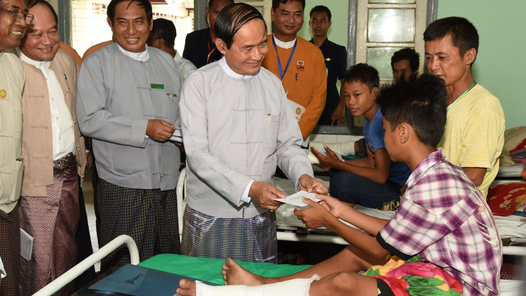 President U Win Myint presents cash assistance to a patient receiving treatment at the Pathein People's Hospital (500-bed).  Photo: MNA