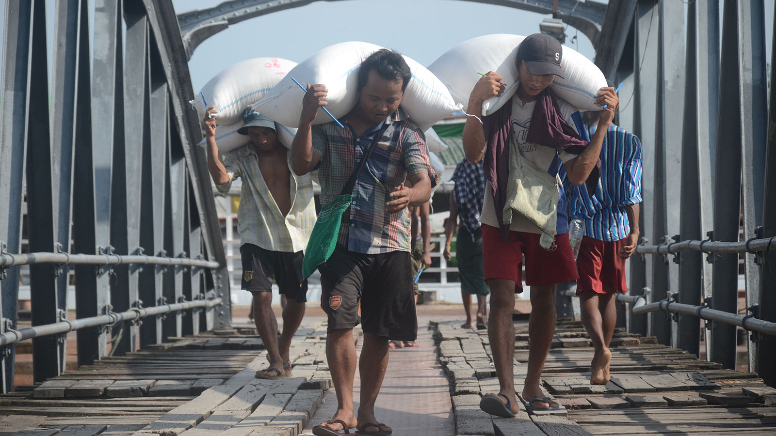 Workers carry bags of rice at the Botahtaung Jetty in Yangon. Photo: Phoe Khwar