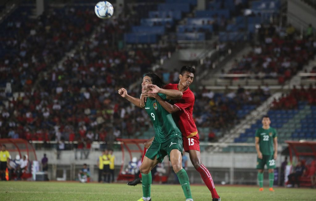 Bolivia (green) attempts to head butt the ball while Myanmar (red) holds him back in yesterday's international friendly match at Thuwunna Stadium in Yangon yesterday.Photo:MFF
