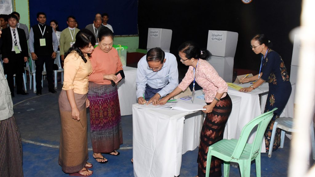 President U Win Myint, First Lady Daw Cho Cho fill in the form to get ballots for the by-election in Tamway Township yesterday. Photo: MNA