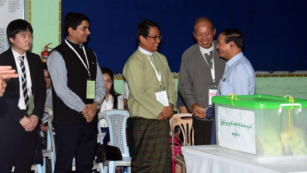 President U Win Myint greets officials of the polling station and international election observers after casting his vote for a vacant seat of Pyithu Hluttaw. Photo: MNA