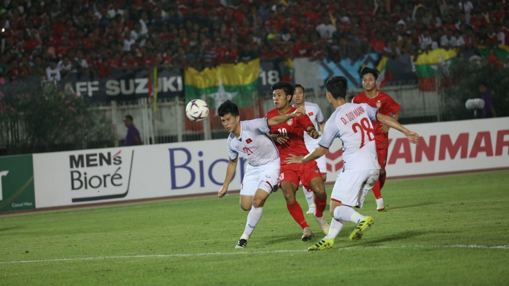 Myanmar's striker Aung Thu(red) tries to break through Viet Nam's defence at the AFF Suzuki group match at Thuwunna Stadium in Yangon on 19 November.Photo:MFF