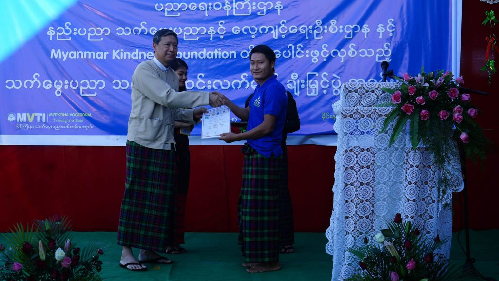 Union Minister for Education Dr. Myo Thein Gyi presents a course completion certificate to a TVET trainee in Myitkyina.photo: mna