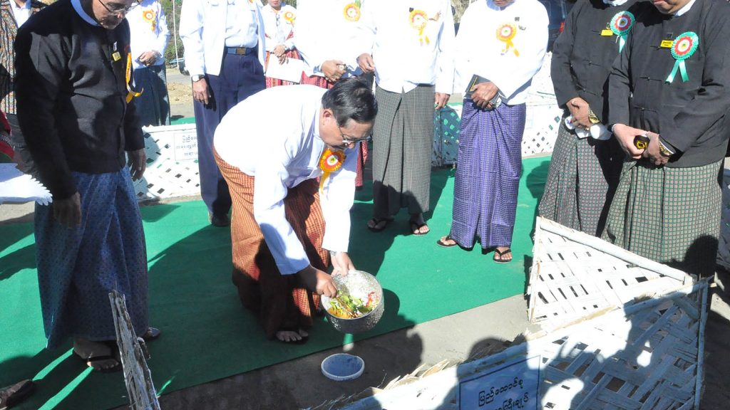 Union Chief Justice U Htun Htun Oo sprinkles scented water on the stake driven for construction of Chin State High Court.Photo: MNA
