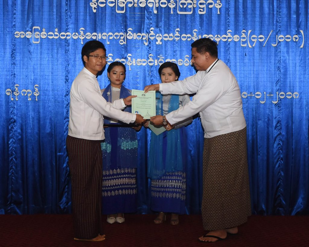 Ministry of Foreign Affairs Permanent Secretary U Myint Thu presents  certificate to a trainee at the Graduation Ceremony of the Certificate Course in Basic Diplomatic Skills (41/2018) yesterday.Photo: MNA