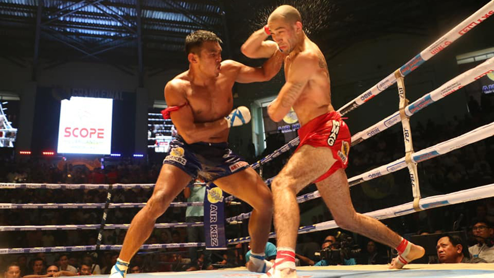 Tun Tun Min (blue) lands a punch on Dave Leduc (red) in Air KBZ Grand Final Championship at the Thein Phyu Stadium in Yangon yesterday.Photo:MLWC