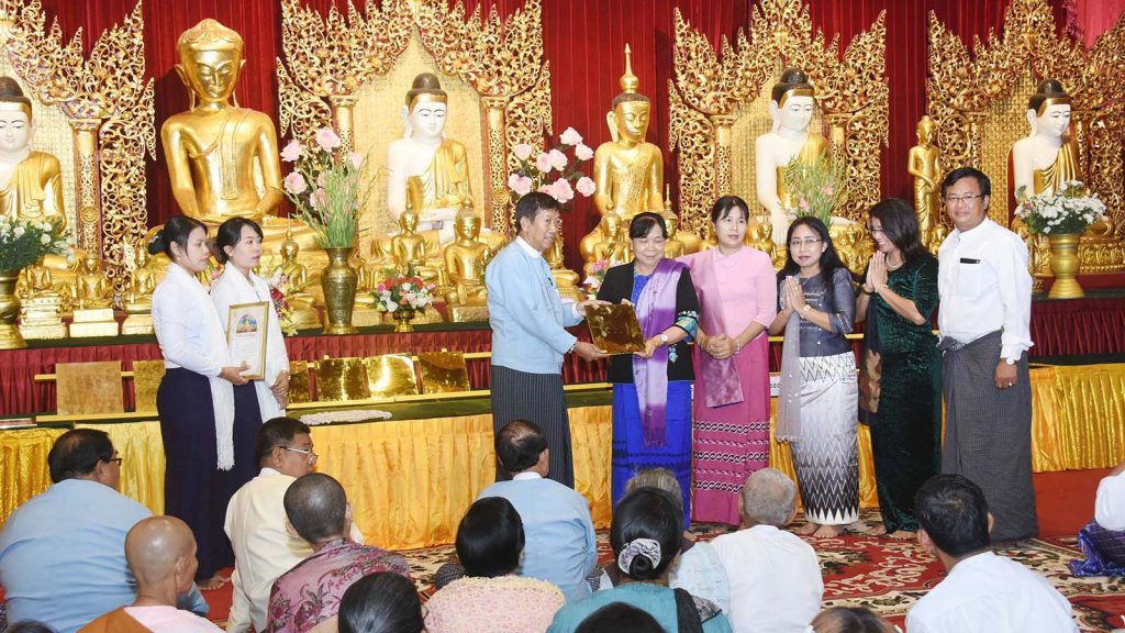 A donor family hands over a gold plate to a member of the Shwedagon Pagoda's Board of Trustees. photo: mna