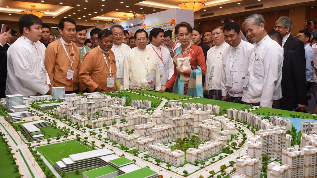 State Counsellor Daw Aung San Suu Kyi looks at a scale model of a housing project exhibited at the Invest Myanmar Summit 2019 in Nay Pyi Taw yesterday.Photo: MNA
