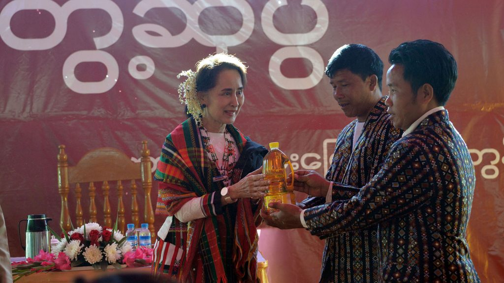 State Counsellor Daw Aung San Suu Kyi presents cooking oil to two representatives of Chin ethnic people from Haka Lay North and Haka Lay South villages during the meeting with local people yesterday. Photo: Thet Aung