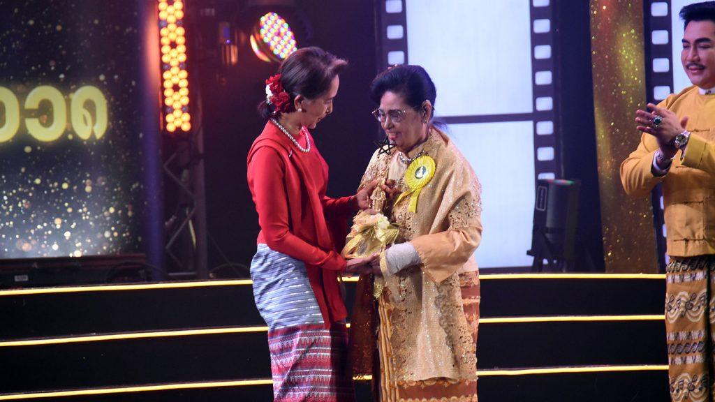 State Counsellor Daw Aung San Suu Kyi presents the lifetime achievement award to five time academy award winner Sithu Daw Myint Myint Khin at 2018 Myanmar Academy Awards event yesterday.Photo: MNA