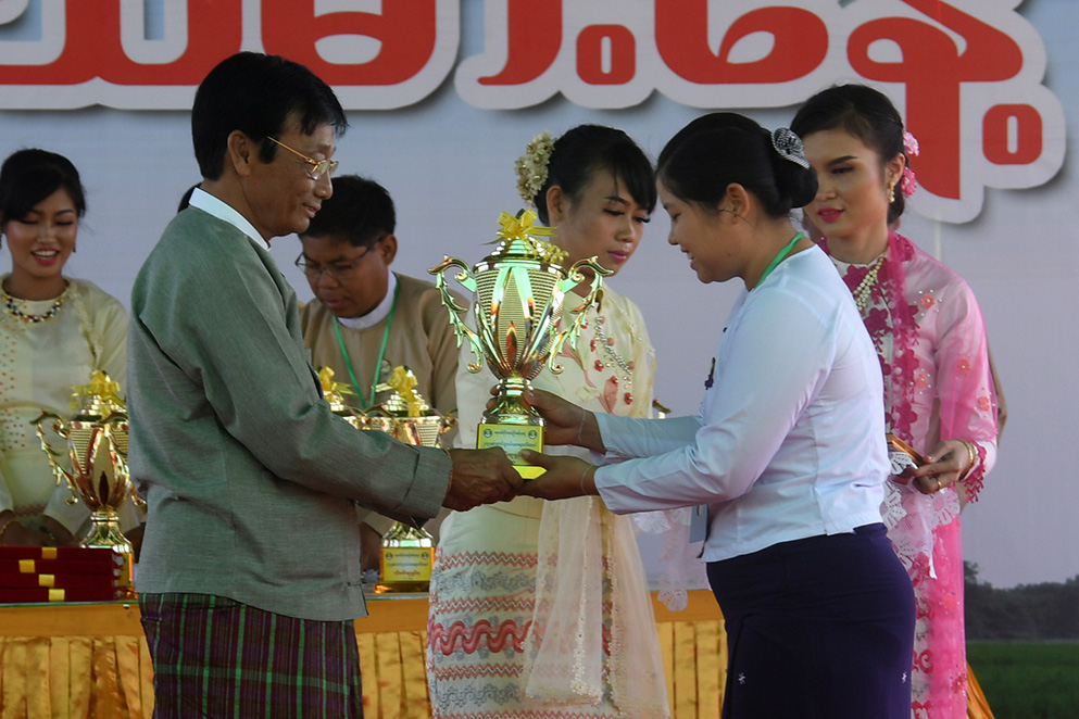 Deputy Minister U Hla Kyaw presents the award to an outstanding staff.  Photo : MNA