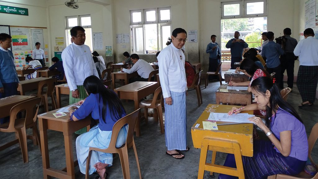 Union Civil Service Board Chairman Dr. Win Thein inspects civil servants taking a test.