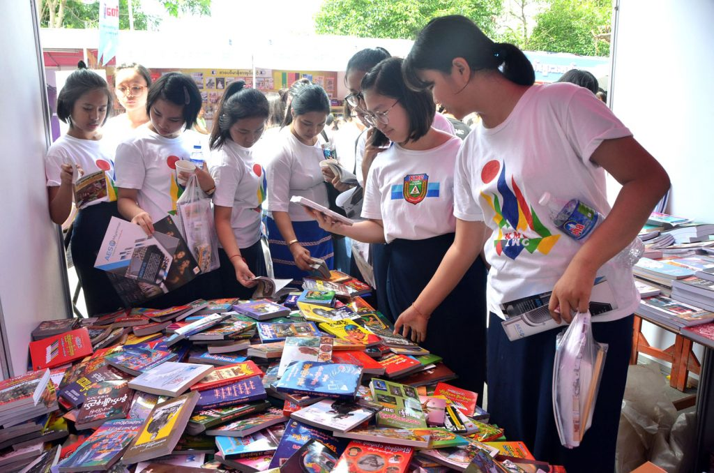 School children choose books at the the All Round Development of Youth Festival in Mandalay on 14 August, 2018.PHOTO: MNA