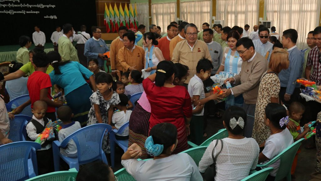 Union Minister Dr. Win Myat Aye presents gifts to the child at the meeting hall of Mon State Government in Mawlamyaing yesterday.Photo: MNA