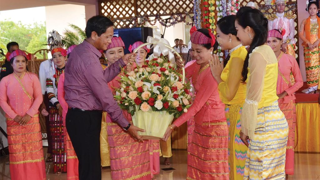 Vice President U Henry Van Thio presents the flower bouquet to artistes after the  public entertainments programme at National Landmark Garden in Nay Pyi Taw yesterday.Photo: MNA