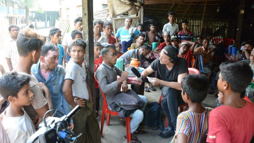 A foreign journalist interviews locals at Thae Chaung IDP camp in Sittway. Photo: MNA