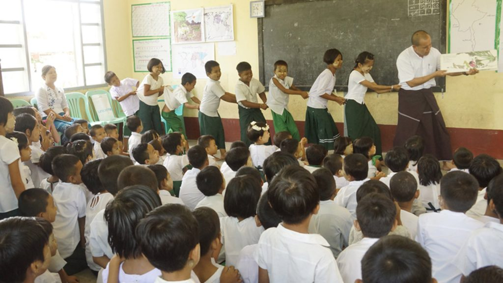In the left picture, a teacher acts out the story of cooperation between forest friends, borrowed from the mobile library organized by the Information and Public Relations Department and Shanti Volunteer Association, with students. photo: mna
