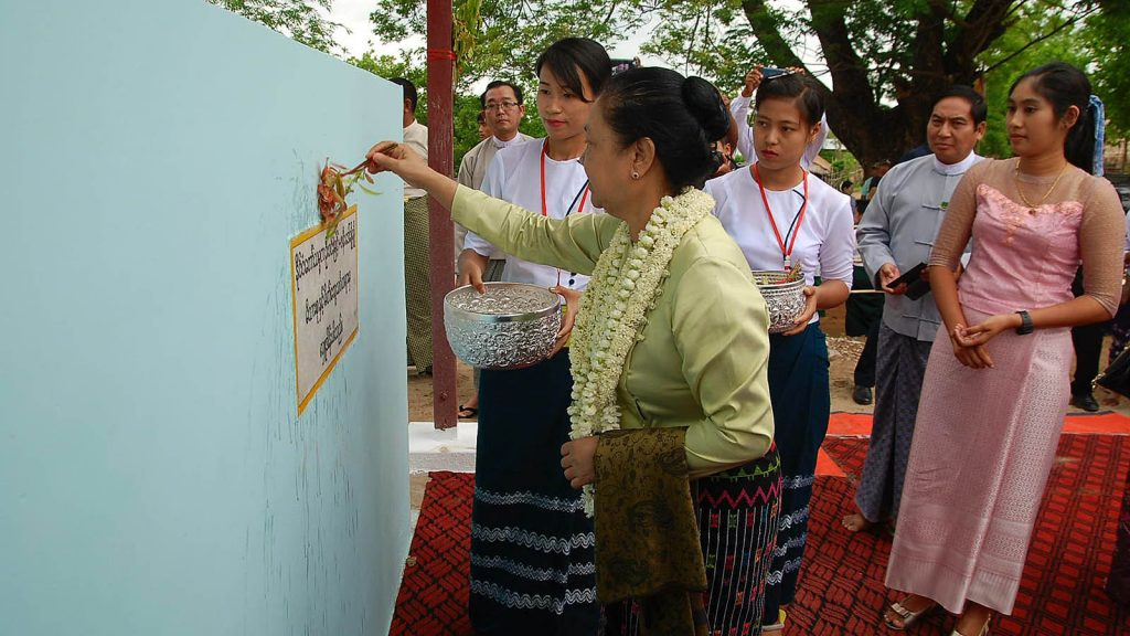 First lady Daw Cho Cho sprinkles scented water on the donor recognition wall at the donation ceremony of artisan tube-well and a concrete tank at Shwelu-Ai Village in KhinU Township yesterday.Photo: MNA